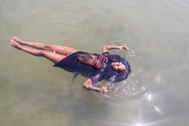 Bela jovem afro-americana flutuando em uma piscina