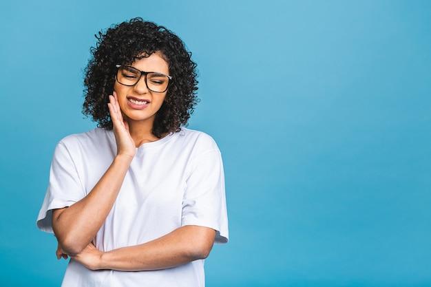 Bela jovem afro-americana sobre um fundo isolado tocando a boca com a mão com uma expressão dolorida por causa de uma dor de dente
