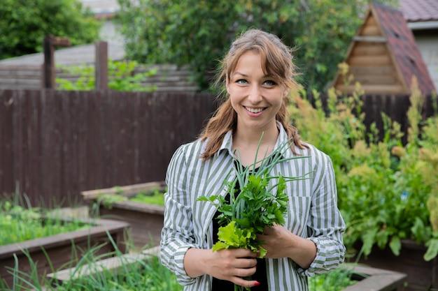 Bela jovem agricultora com ervas frescas da colheita nas mãos