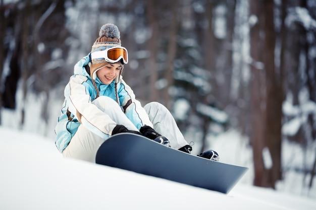Bela jovem ajustando as amarras de snowboard sentada em uma pista de esqui
