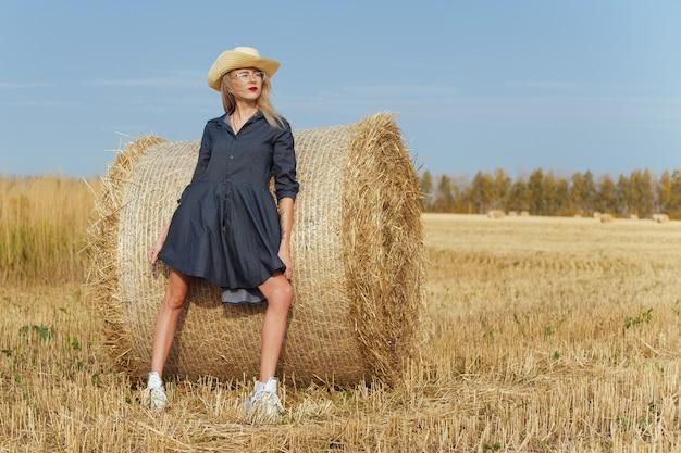 Bela jovem aldeã posando com um vestido perto de um fardo de feno em um campo