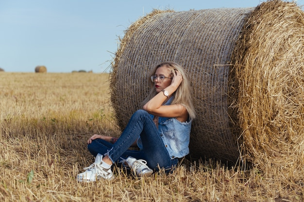 Bela jovem aldeã posando de jeans perto de um fardo de feno em um campo