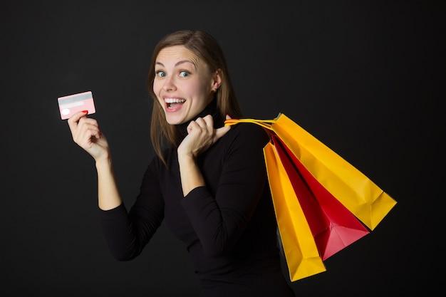 Bela jovem alegre com pacotes e um cartão de crédito nas mãos em um fundo preto