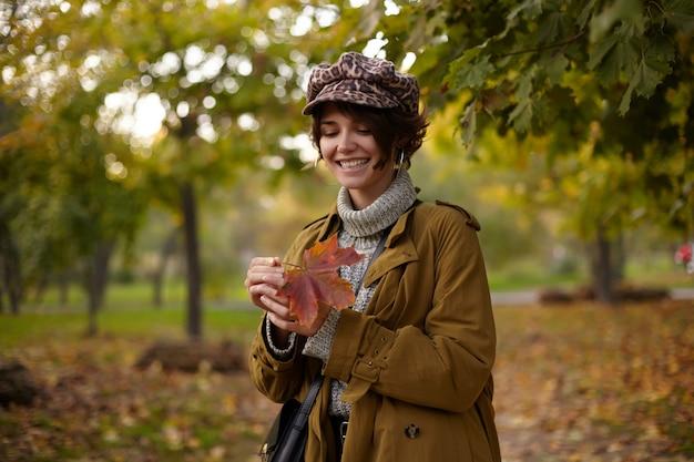Bela jovem alegre de cabelos castanhos com penteado casual, segurando uma folha amarelada nas mãos e sorrindo amplamente enquanto espera por seus amigos no jardim da cidade