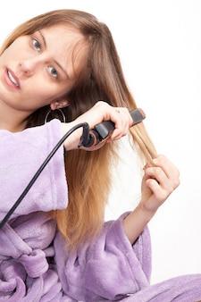 Bela jovem alisando o cabelo dela