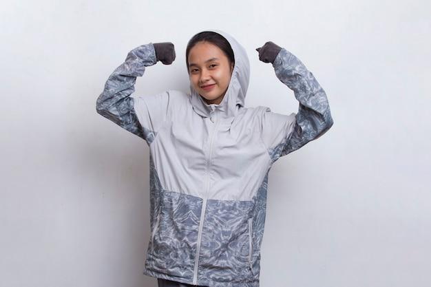 Bela jovem alpinista asiática com uma mochila fazendo gestos fortes, isolado no fundo branco
