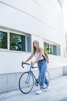 Bela jovem andando com a bicicleta na calçada