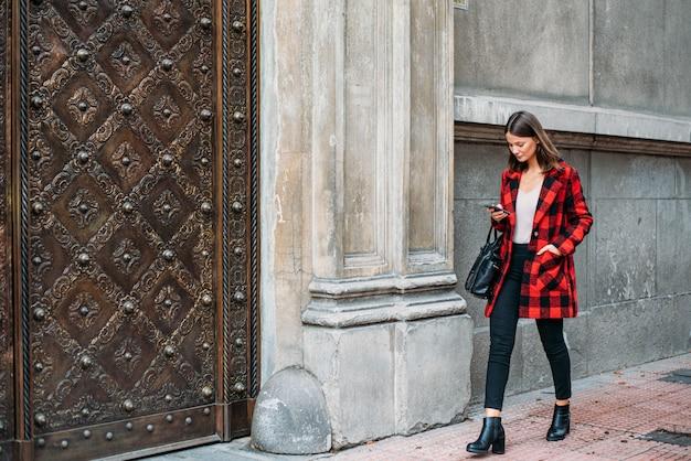 Bela jovem andando na rua usando o telefone