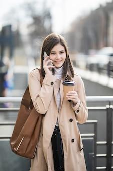 Bela jovem andando pela rua, segurando o telefone e a xícara de café
