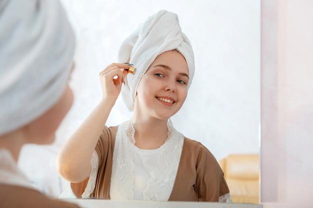 Bela jovem aplica soro de óleo no conta-gotas para cuidados com a pele no banheiro perto do espelho. produto cosmético de autocuidado na rotina matinal. adolescente jovem bonita no manto com uma toalha na cabeça.