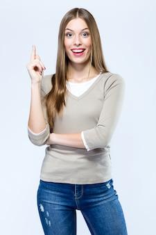 Bela jovem apontando para cima sobre fundo branco.