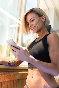 Bela jovem apto mulher usando smartphone no ginásio. ela tem tatuagens