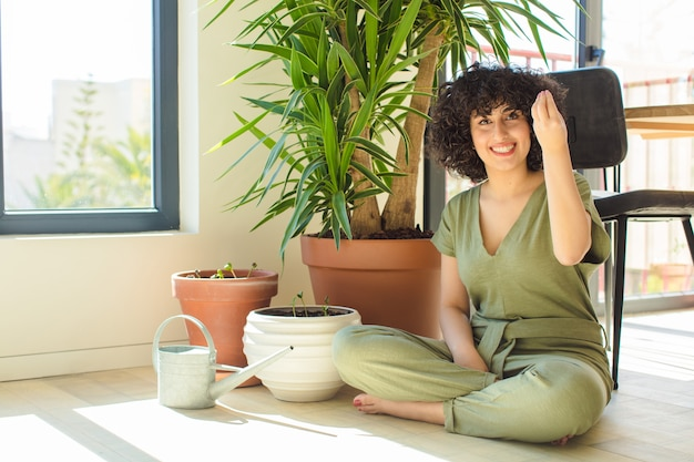 Bela jovem árabe em casa, com regador e plantas