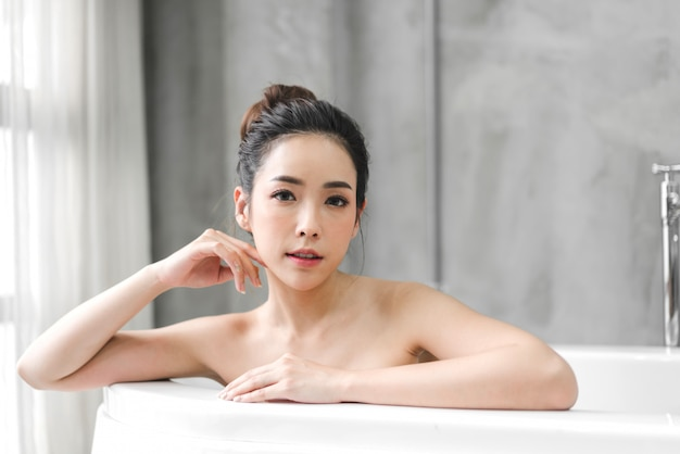 Bela jovem ásia desfrutar de relaxar tomando banho com espuma de bolha na banheira no banheiro