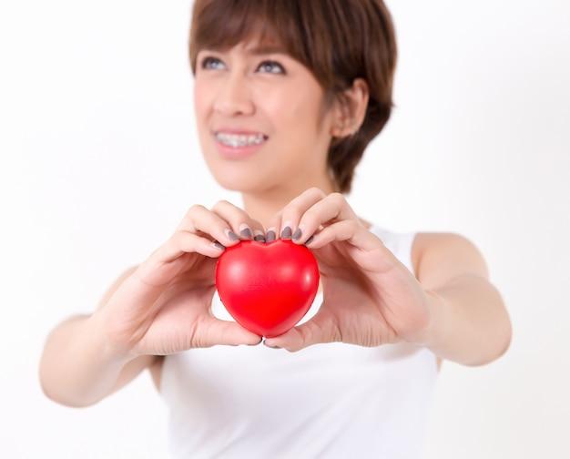 Bela jovem ásia mulher com coração vermelho