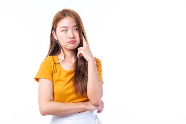 Bela jovem asiática apontou um dedo para a cabeça dela e sorriu isolado no fundo branco. ela mostra que está elaborando novos planos para realizar seu trabalho