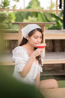 Bela jovem asiática bebendo mocktail de frutas vermelhas no café no verão
