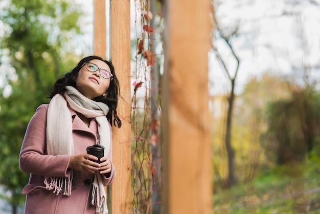 Bela jovem asiática bebendo uma bebida quente em um copo de papel descartável ao ar livre. menina vestida com casaco rosa e lenço branco. lo