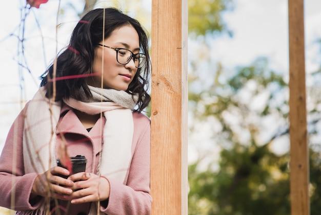 Bela jovem asiática bebendo uma bebida quente em um copo de papel descartável ao ar livre. menina vestida com casaco rosa e lenço branco. olhar para baixo.