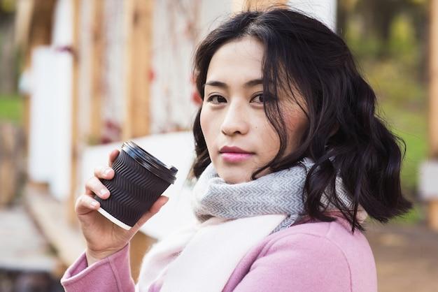 Bela jovem asiática bebendo uma bebida quente em um copo de papel descartável ao ar livre. uma garota olha para a câmera. menina vestida com casaco rosa e lenço branco.