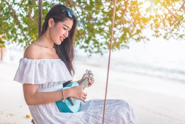 Bela jovem asiática brincando com ukulele e relaxa na praia