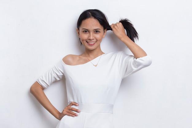 Bela jovem asiática com cabelo forte e saudável isolado no fundo branco.