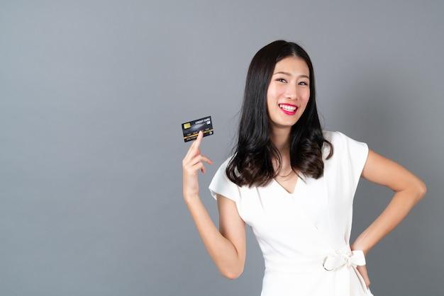 Bela jovem asiática com cara feliz e apresentando cartão de crédito na mão, mostrando confiança e segurança para fazer o pagamento