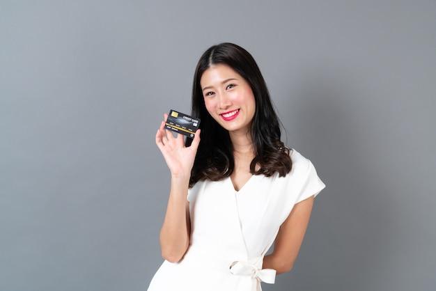 Bela jovem asiática com cara feliz e apresentando o cartão de crédito na mão, mostrando confiança e segurança para fazer o pagamento em cinza