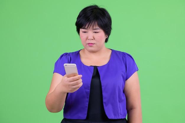 Bela jovem asiática com excesso de peso contra chroma key com parede verde