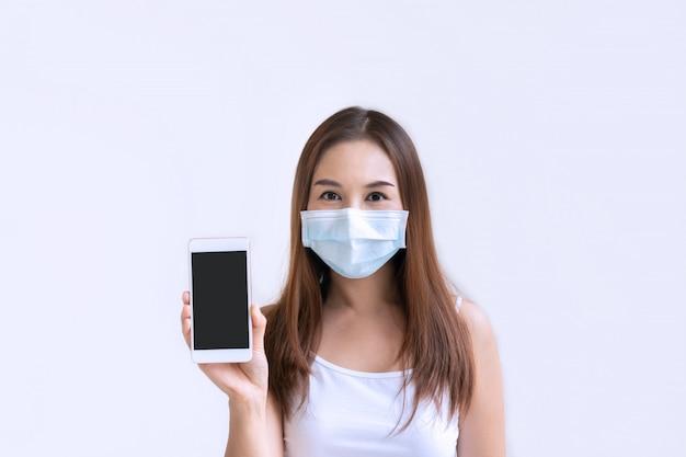 Bela jovem asiática com máscara protetora segurando o smartphone para espaço de cópia em fundo branco