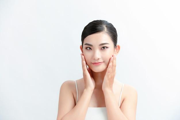 Bela jovem asiática com pele limpa, fresca na parede branca,