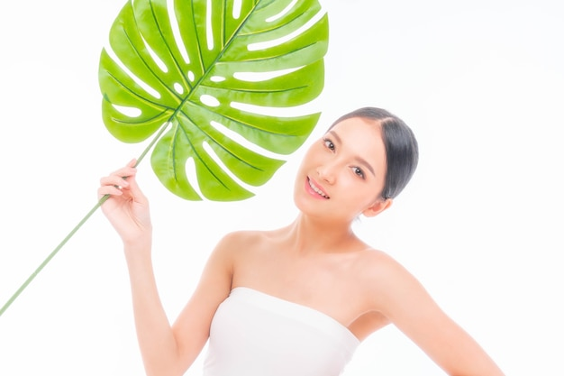 Bela jovem asiática com pele limpa, pele fresca segurando uma folha tropical verde nas mãos sobre fundo branco - foto de beleza de mulher asiática tratamento facial, cosmetologia, beleza e conceito de spa