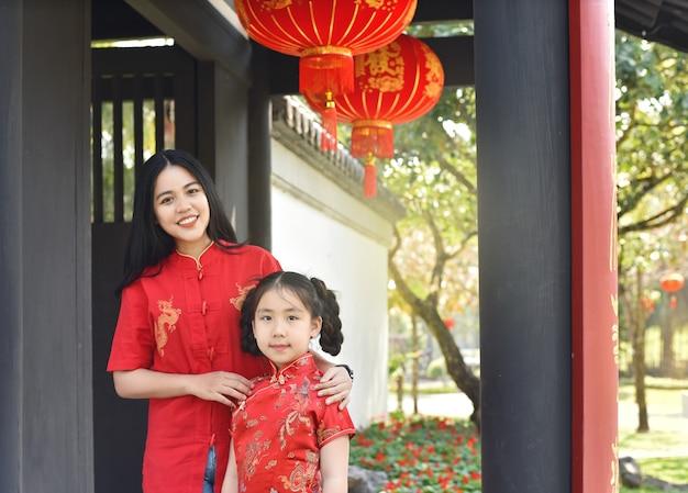 Bela jovem asiática com uma garota celebrando o ano novo lunar em casa