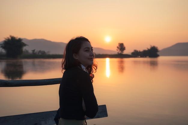 Bela jovem asiática curtindo com o nascer do sol no lago da montanha pela manhã