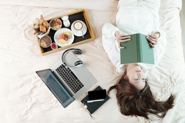 Bela jovem asiática deitada na cama ao lado do laptop e da bandeja do café da manhã e pensando depois de ler um artigo instigante no livro