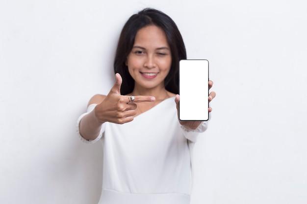 Bela jovem asiática demonstrando celular isolado no fundo branco