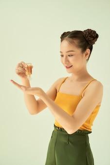 Bela jovem asiática derramando desinfetante para as mãos isolado na luz de fundo.