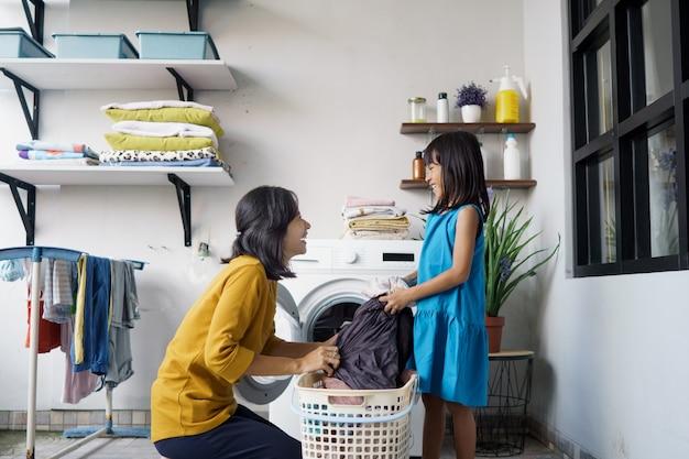 Bela jovem asiática e ajudante de menina criança estão lavando roupa em casa.
