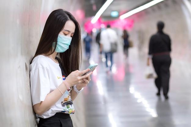 Bela jovem asiática em pé no túnel do metrô e usa máscara facial como um novo conceito normal