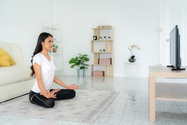 Bela jovem asiática em roupas esportivas, fazendo ioga enquanto relaxa na sala de estar em casa
