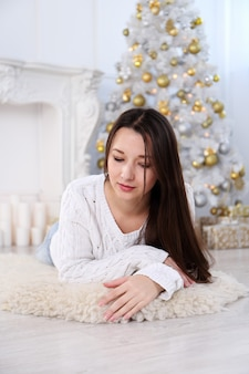 Bela jovem asiática em uma sala decorada com árvore de natal