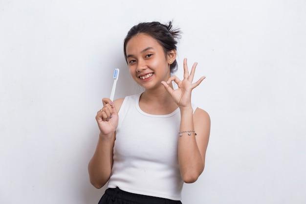 Bela jovem asiática escovando os dentes isolados no fundo branco