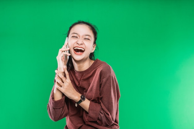 Bela jovem asiática está falando ao telefone com expressão riso isolado contra o fundo verde