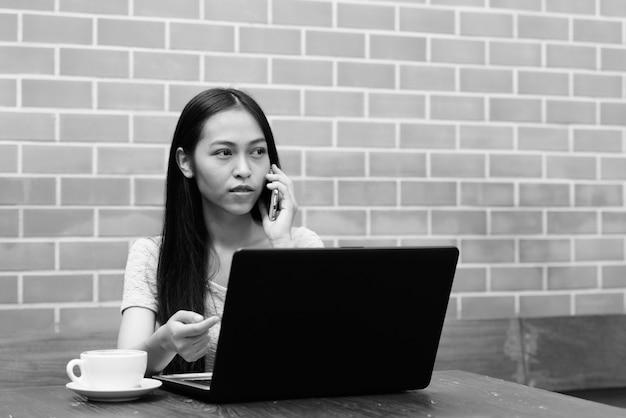 Bela jovem asiática falando no celular enquanto pensa com o laptop na mesa de madeira na parede de tijolos