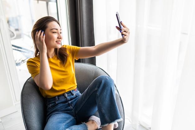 Bela jovem asiática fazendo selfie com seu telefone inteligente e sorrindo enquanto está sentada em uma grande cadeira confortável em casa