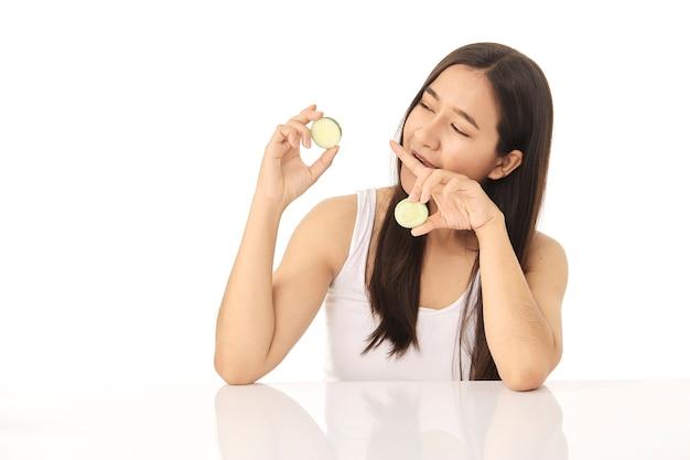 Bela jovem asiática limpando o rosto de beleza, usando loção de limpeza de fatias de pepino e tônico facial para remover a maquiagem. uma linda garota tem uma bela pele facial.