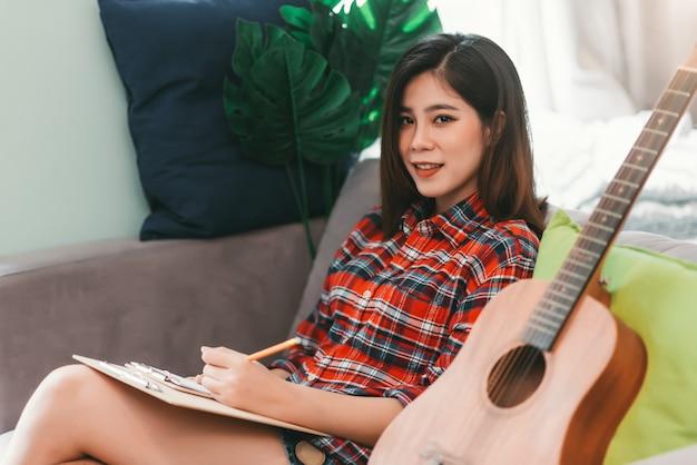 Bela jovem asiática no sofá com guitarra