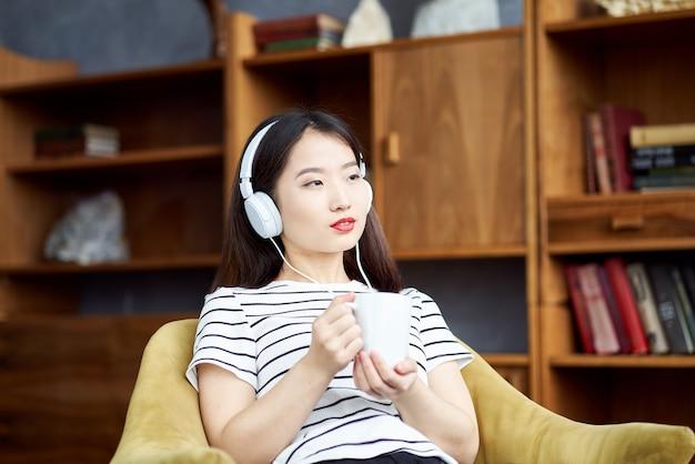 Bela jovem asiática ouvindo música com fones de ouvido, sentada na cadeira