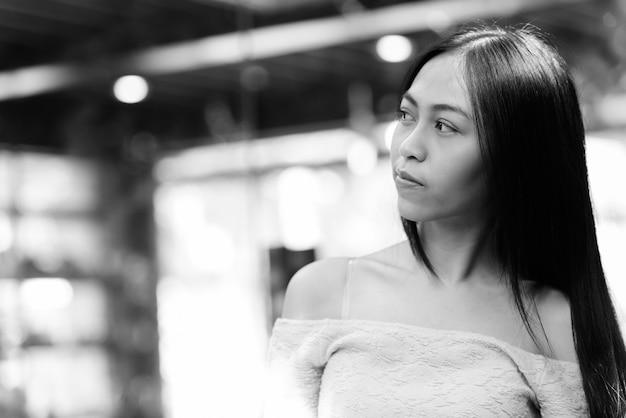 Bela jovem asiática pensando enquanto olha a distância do lado de fora da cafeteria com janelas de vidro