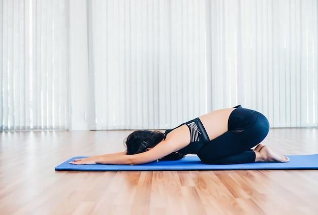 Bela jovem asiática pratica ioga, treinamento de exercício de pilates em casa
